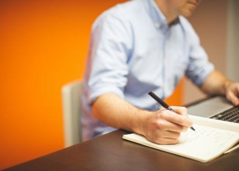 Bilde av ein mann som sitt og arbeider framfor ein PC