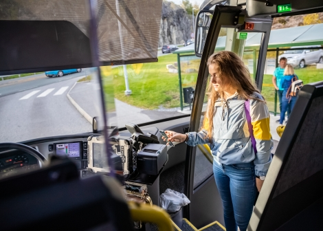 Foto av ung kvinne som går ombord på buss