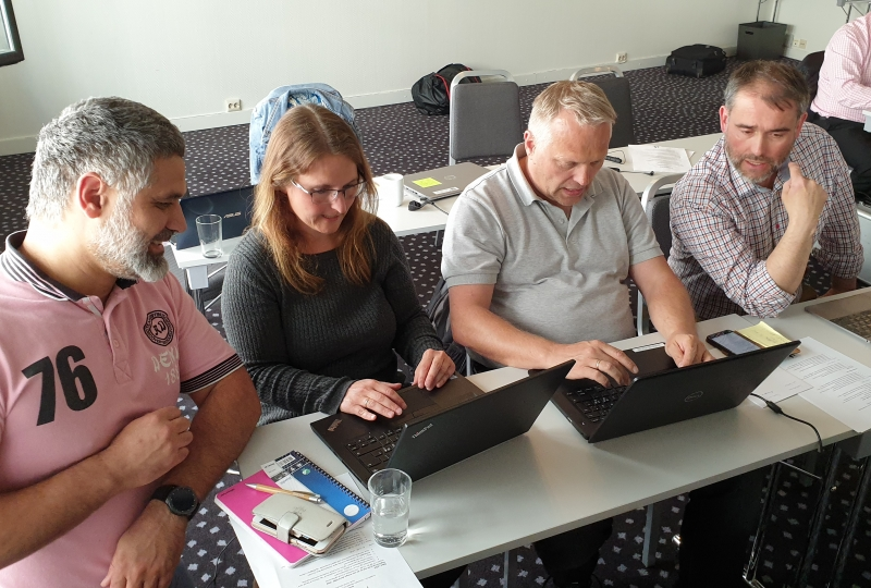Foto av fire personer som jobber på datamaskin