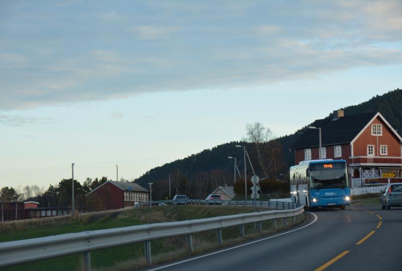 Bilde av ein buss som kjem køyrande på ein veg