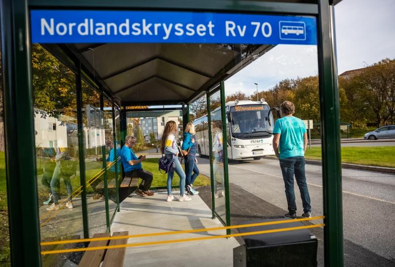 Foto av ein buss og passasjerar ved ein busshaldeplass