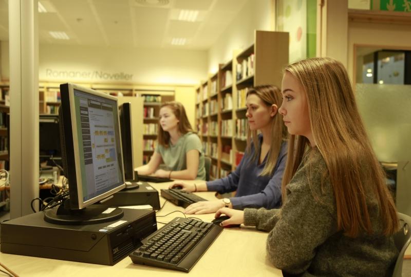 Bilde av tre elevar som sitt framfor kvar sin PC