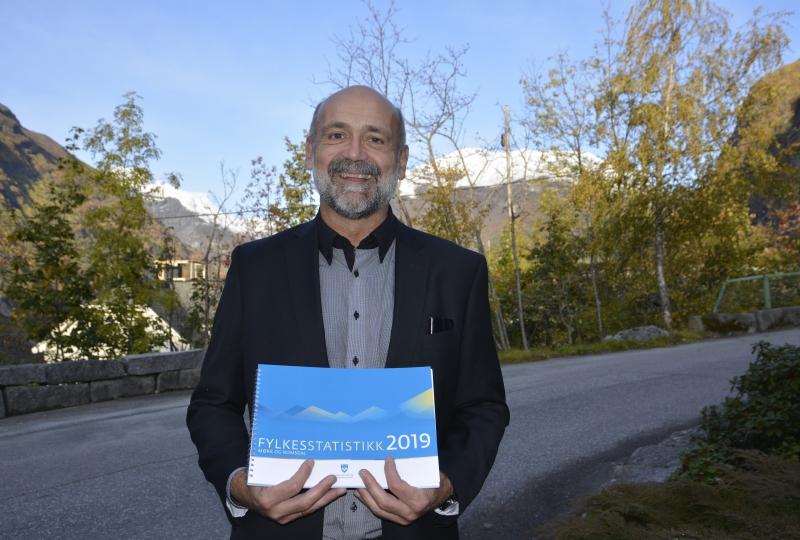 Foto av fylkesplansjef Ole Helge Haugen som holder den trykte utgaven av fylkesstatistikken